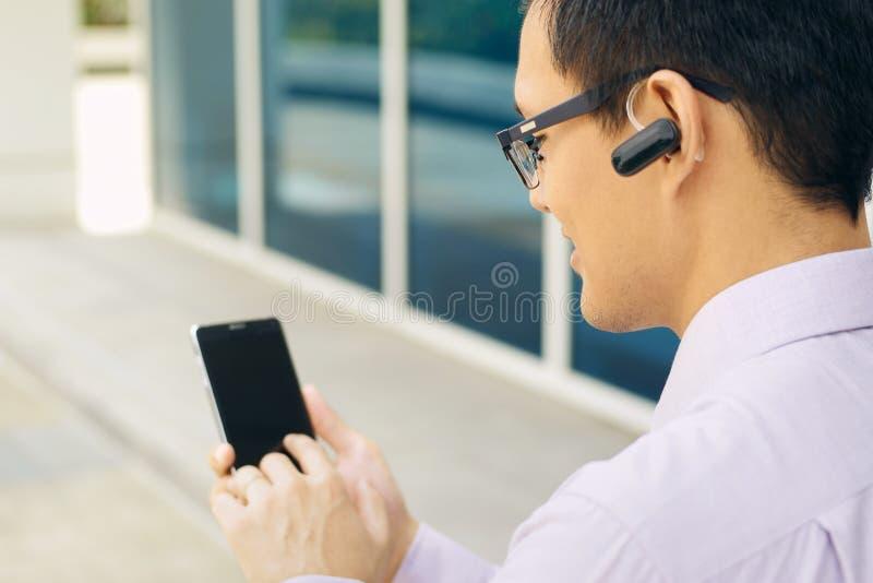 Telefone de Calling On Mobile do homem de negócios com auriculares de Bluetooth fotografia de stock