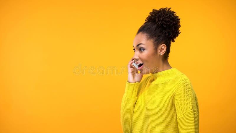 Telefone de fala da mulher afro-americana alegre, excitado para ouvir a boa not?cia, bisbolhetice foto de stock