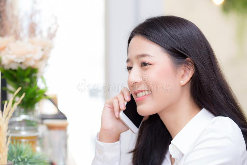 Telefone de fala da mulher asiática nova bonita e sorriso na cafetaria, mulher de negócios que senta-se no tempo livre do café imagem de stock