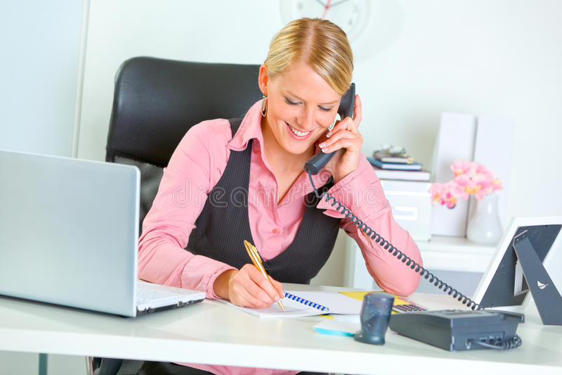 Telefone de fala de sorriso da mulher de negócio fotos de stock