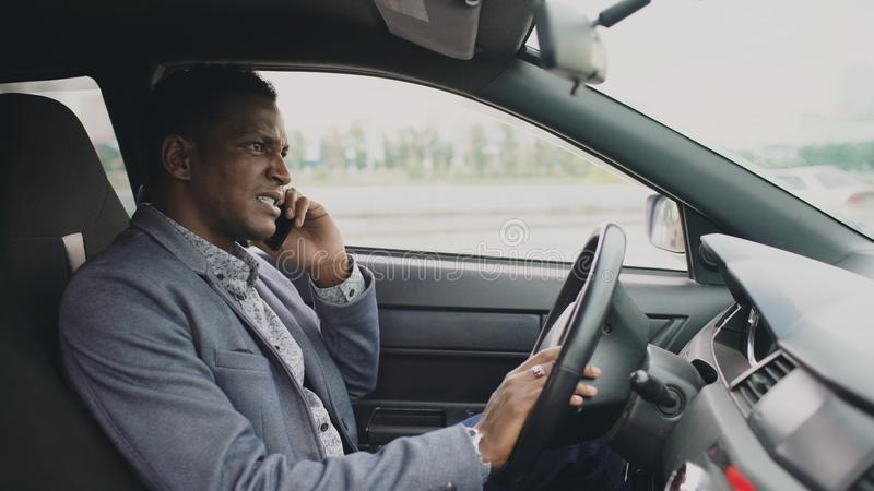 Telefone de fala do homem de negócios irritado da raça misturada ao sentar-se dentro de seu carro fora imagens de stock royalty free