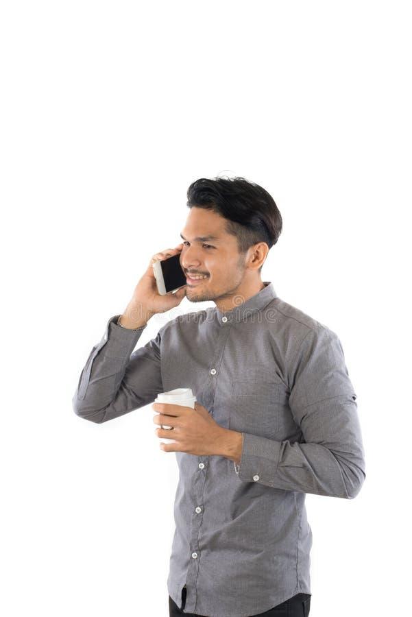 Telefone de fala do homem novo do moderno quando copo de café no isolat das mãos imagens de stock royalty free