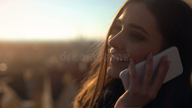 Telefone de fala fêmea novo bonito no skydeck que compartilha das impressões, vagueando imagem de stock