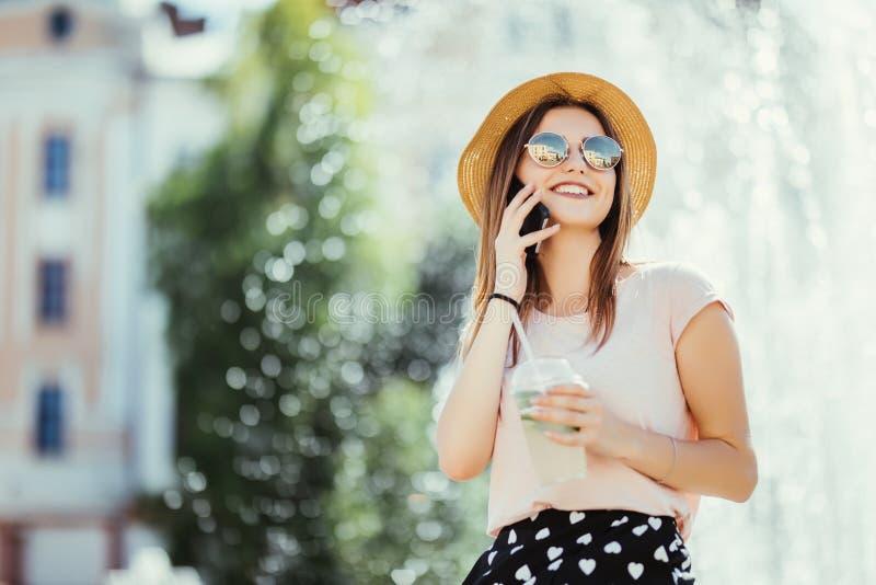 Telefone de fala de sorriso do adolescente da jovem mulher na luz solar exterior bebendo do mojito da rua do verão fotos de stock