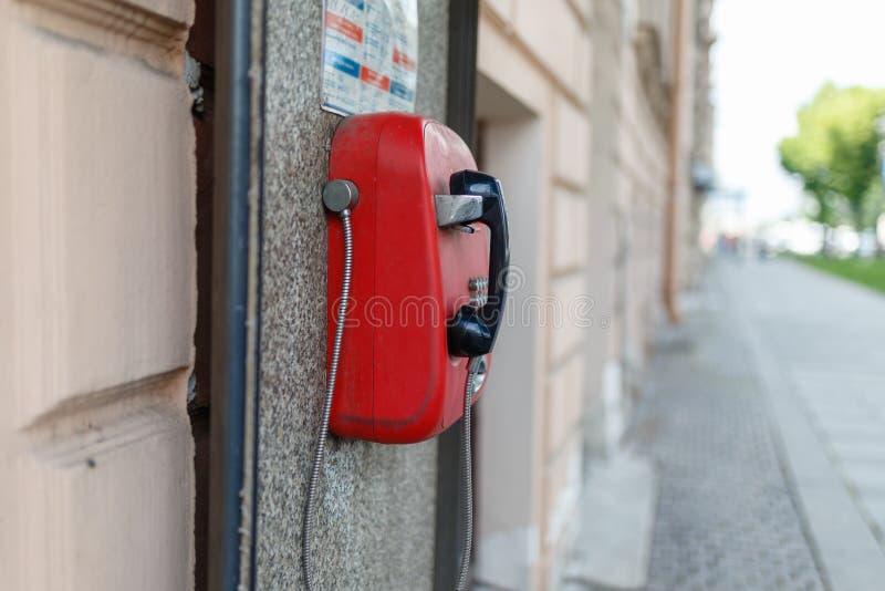 Telefone de pagamento vermelho que pendura na parede do granito da casa velha, contra o contexto do dia de verão ensolarado da pa foto de stock