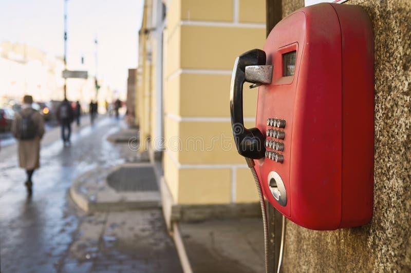 Telefone de pagamento vermelho que pendura na parede do granito da casa velha, em t fotografia de stock