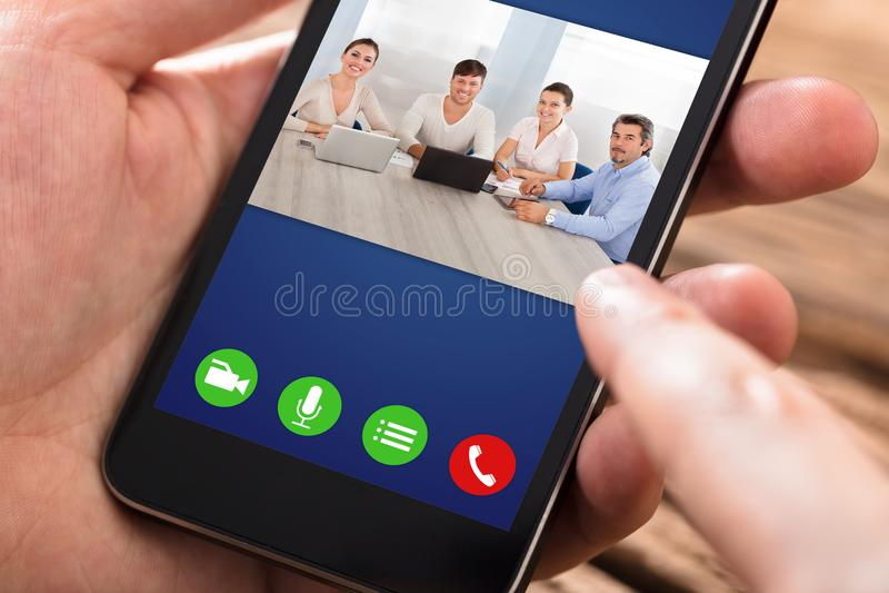 Telefone de Person Video Conferencing On Mobile fotografia de stock
