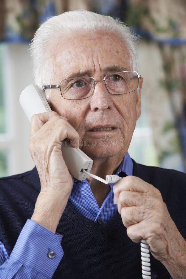 Telefone de resposta preocupado do homem superior em casa fotografia de stock