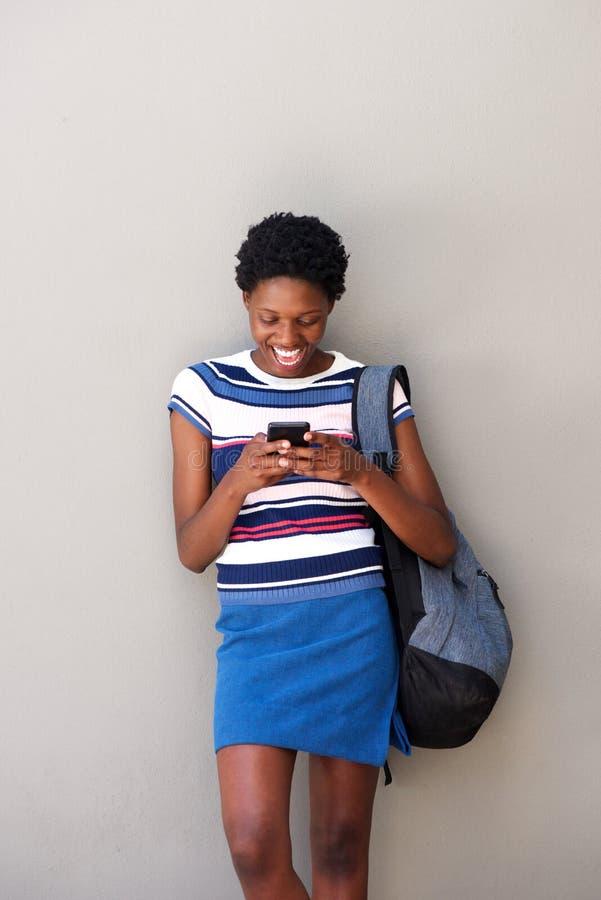Telefone de utilização fêmea africano novo e riso no fundo cinzento foto de stock