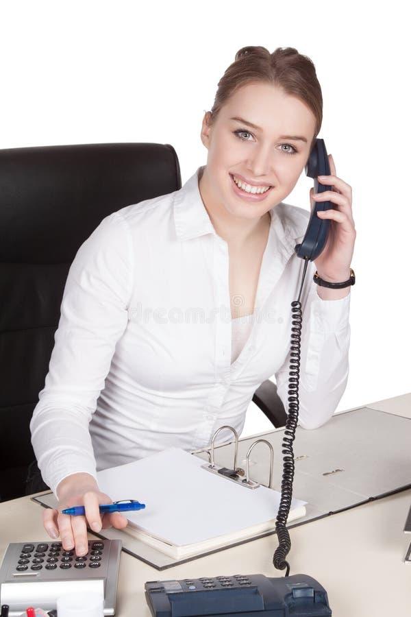 Telefone der jungen Frau am Schreibtisch stockbild