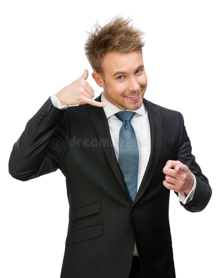 Telefone do homem de negócios que gesticula pontos com dedo imagem de stock