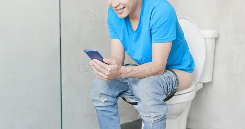 Telefone do uso do homem no toalete foto de stock royalty free