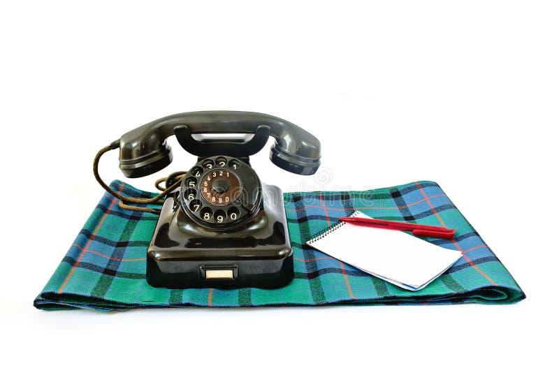 Telefone do vintage na manta de tartã com pena vermelha e no bloco de notas com copyspace fotografia de stock