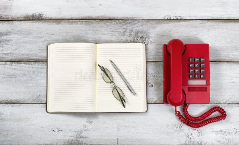 Telefone e bloco de notas vermelhos do vintage com vidros da pena e de leitura no ru foto de stock