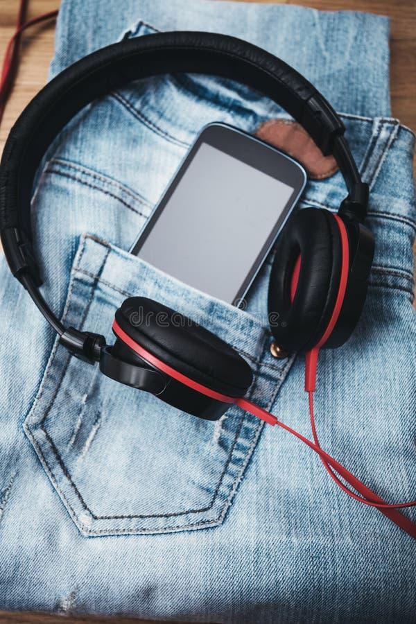 Telefone e calças de ganga do smat dos fones de ouvido fotos de stock