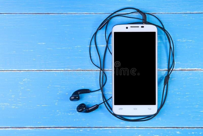 Telefone e fone de ouvido espertos no fundo de madeira azul fotos de stock