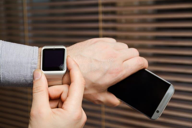Telefone e relógio esperto em uma mão masculina foto de stock