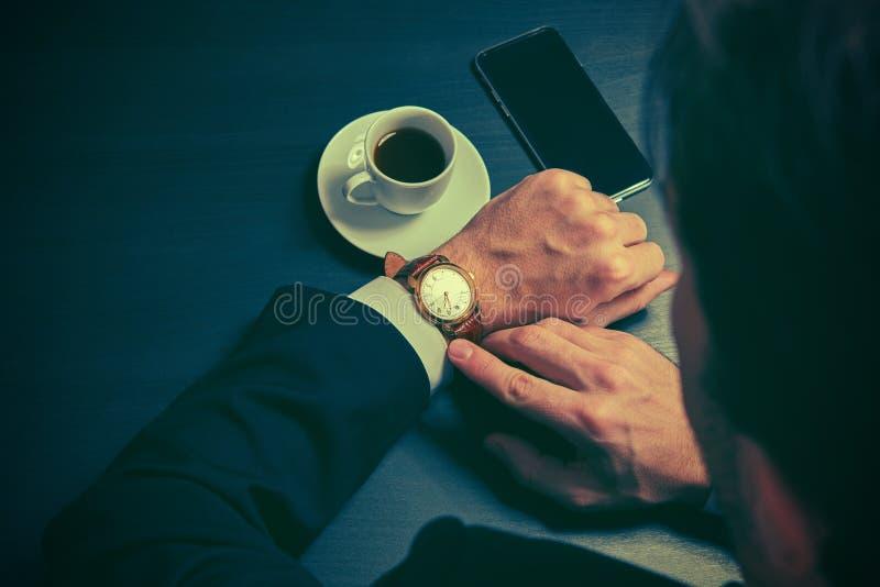 Telefone e uma xícara de café nas mãos de um homem de negócios em cores escuras imagem de stock royalty free