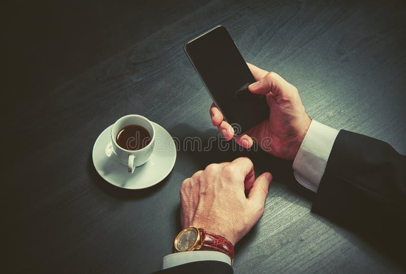 Telefone e uma xícara de café nas mãos de um homem de negócios em cores escuras foto de stock