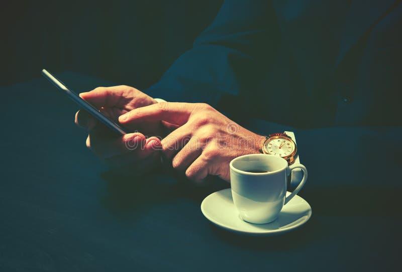 Telefone e uma xícara de café nas mãos de um homem de negócios em cores escuras foto de stock royalty free