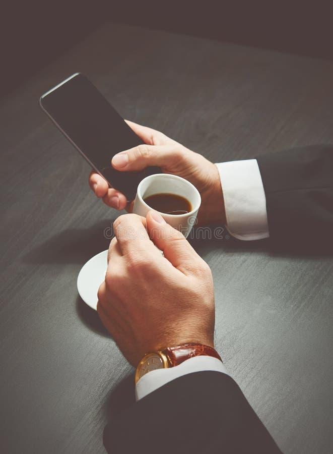 Telefone e uma xícara de café nas mãos de um homem de negócios na obscuridade imagem de stock