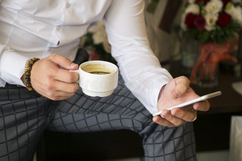 Telefone e uma xícara de café nas mãos de um homem de negócios fotos de stock