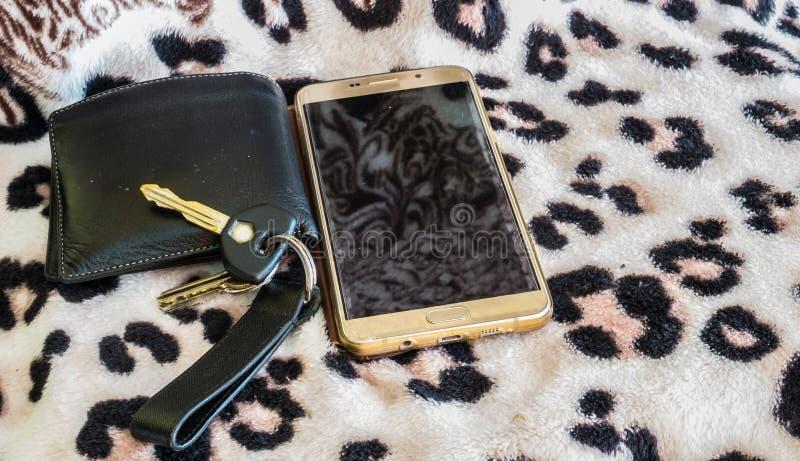 Telefone esperto chave da carteira no fundo platern da pintura do algodão imagens de stock