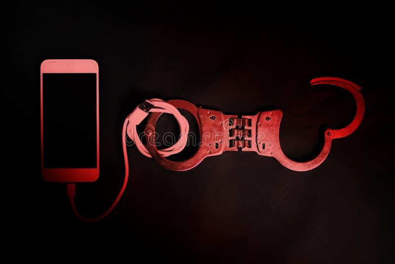 Telefone esperto com a algema na obscuridade imagens de stock