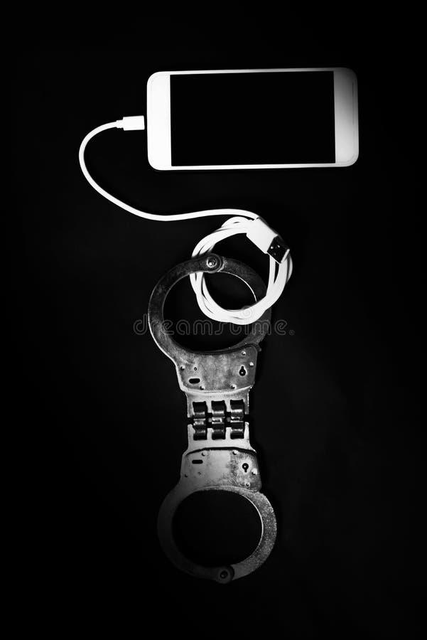 Telefone esperto com a algema na obscuridade imagens de stock royalty free