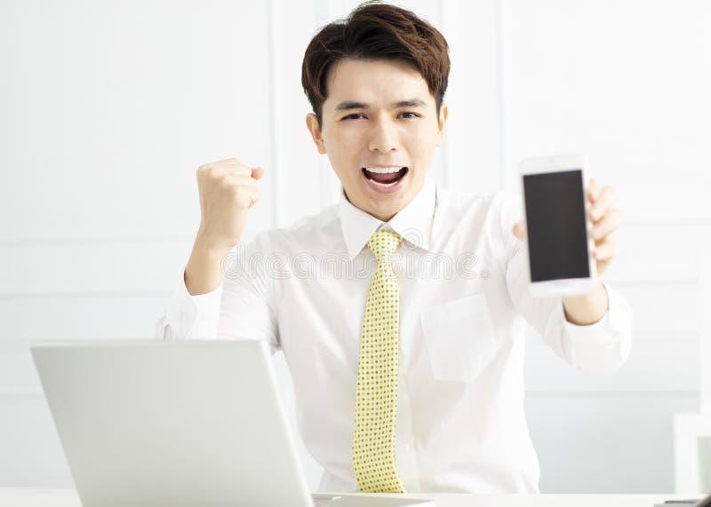 telefone esperto da exibição do homem de negócios no escritório imagem de stock royalty free