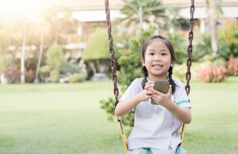 Telefone esperto da mostra bonito da menina no campo de jogos das crianças fotos de stock