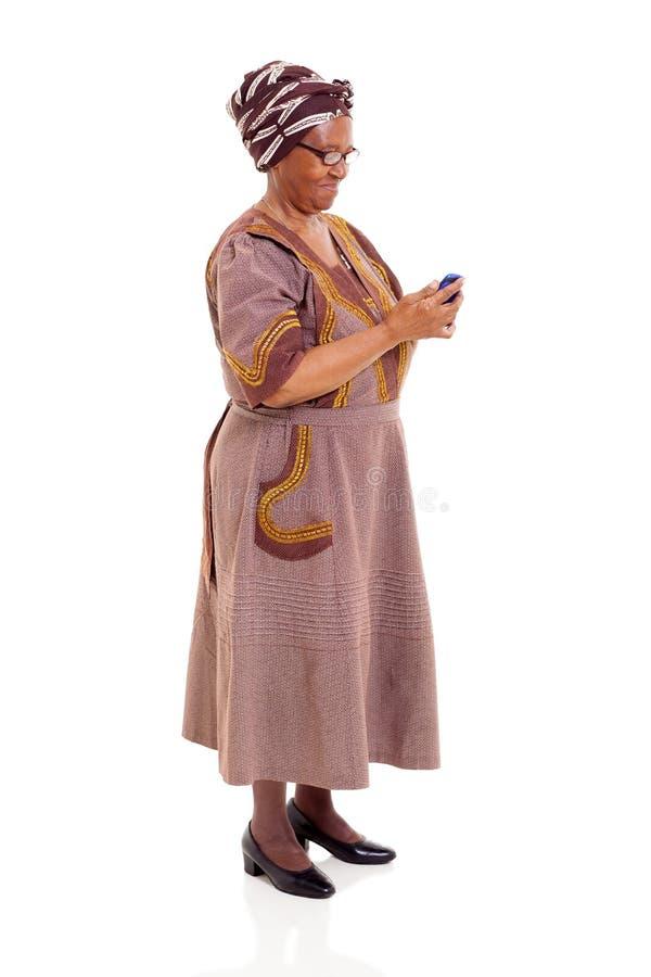 Telefone esperto da mulher africana superior fotos de stock royalty free