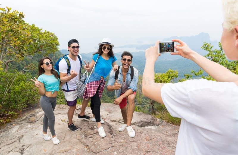Telefone esperto da pilha que toma a foto do grupo alegre do turista com a trouxa sobre a paisagem da parte superior da montanha, fotos de stock royalty free