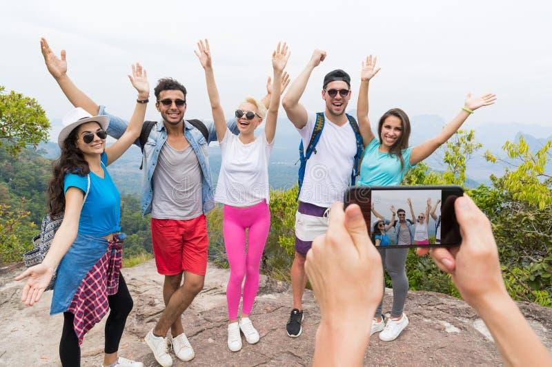 Telefone esperto da pilha que toma a foto do grupo alegre do turista com a trouxa sobre a paisagem da parte superior da montanha, foto de stock