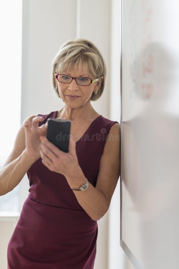 Telefone esperto de Text Messaging On da mulher de negócios ao inclinar-se em Whi fotos de stock