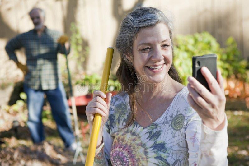 Telefone esperto de utilização exterior dos pares sênior fotografia de stock