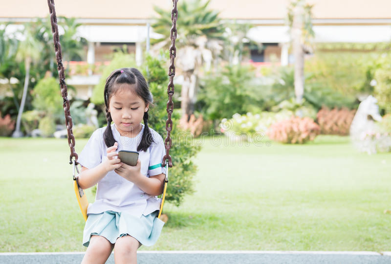 Telefone esperto do jogo bonito da estudante no balanço imagem de stock