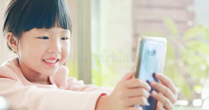 Telefone esperto do uso da menina felizmente foto de stock royalty free