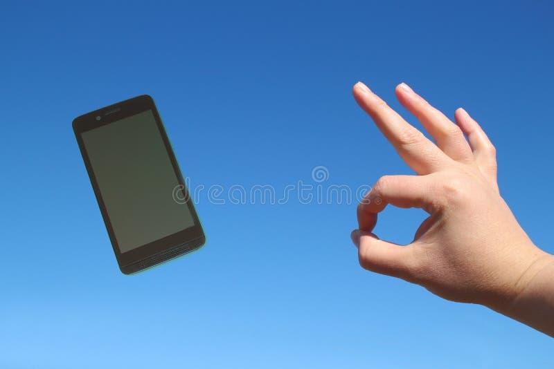 Telefone esperto e gesto aprovado no céu azul fotos de stock royalty free