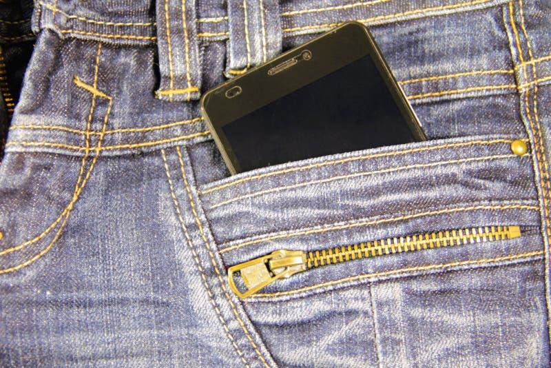 Telefone esperto em um bolso da calças de ganga imagem de stock royalty free