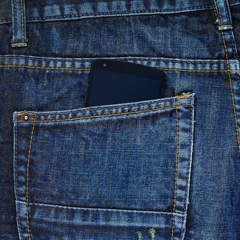 Telefone esperto em um bolso traseiro do calças de brim imagem de stock