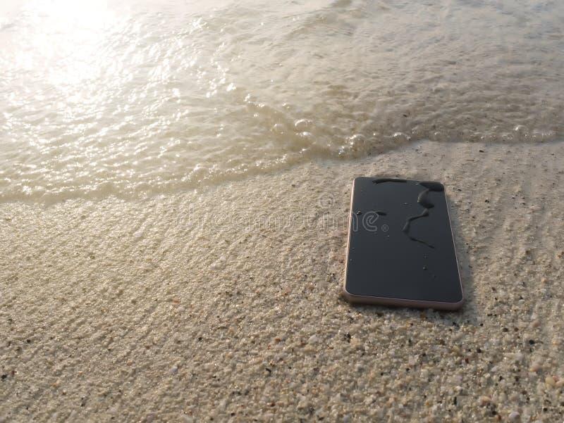 Telefone esperto móvel no Sandy Beach com as ondas macias do fundo do mar Internet do conceito das coisas fotos de stock royalty free