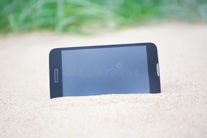 Telefone esperto moderno com a tela vazia na areia foto de stock royalty free