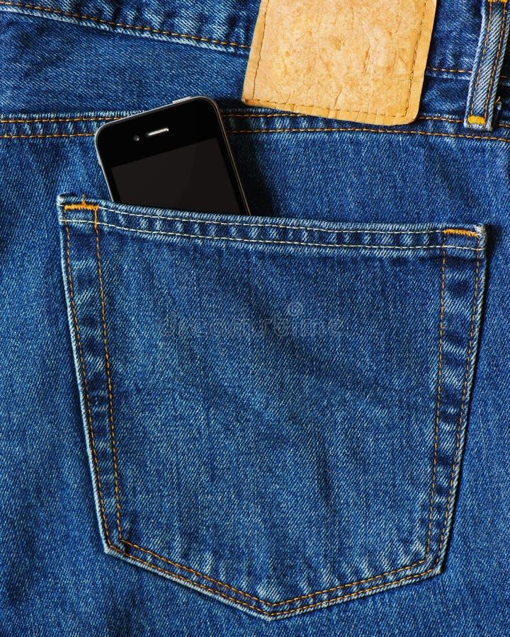 Telefone esperto no bolso traseiro de calças de brim azuis da sarja de Nimes imagens de stock
