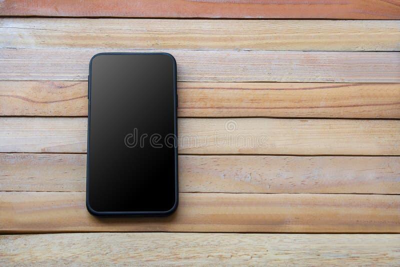 Telefone esperto no fundo de madeira da placa usando o papel de parede para a educação, uma comunicação digital do objeto do conc imagens de stock