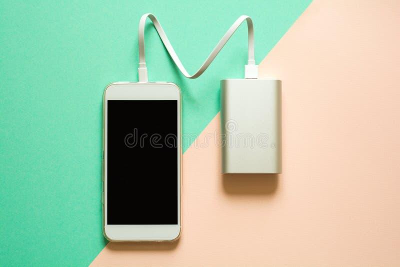 Telefone esperto que carrega com o banco do poder no fundo de papel Recarregando o conceito fotos de stock