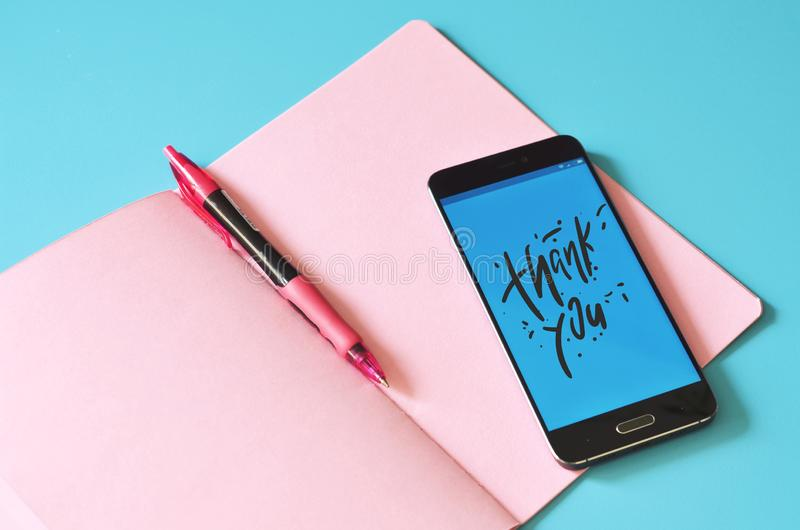 Telefone esperto que indicando agradeça a lhe e ao livro de nota fotografia de stock royalty free
