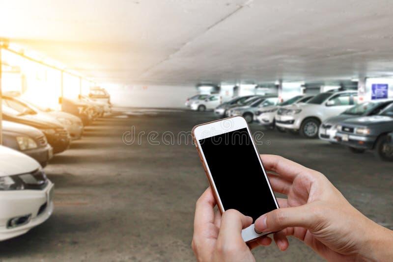 Telefone esperto que mostra a tela vazia na mão do homem com o parque de carros do borrão fotografia de stock royalty free