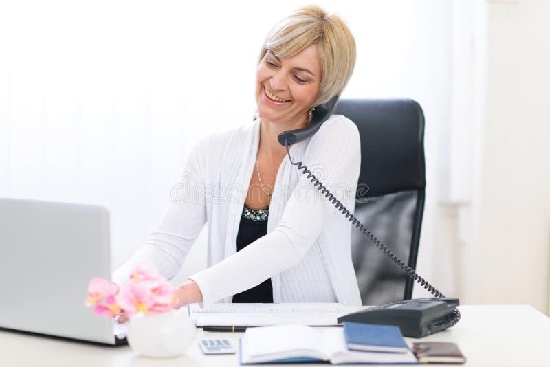 Telefone falador sênior da mulher de negócio fotos de stock royalty free