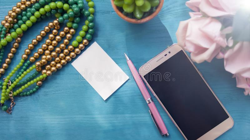 Telefone, flores, uma pena e um caderno Ainda vida 1 Vista superior, o conceito do local de trabalho imagem de stock